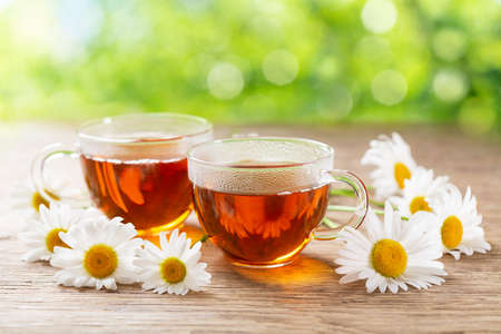 cups of herbal chamomile tea with fresh chamomile flowers on a wooden table