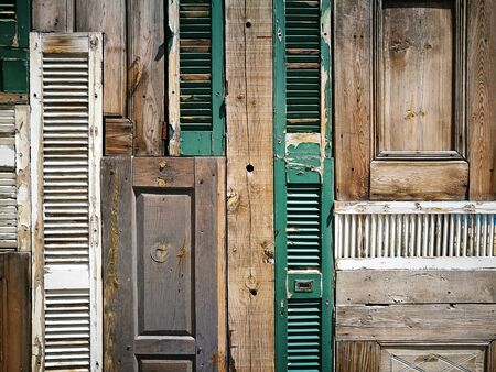 aegis: Old wooden doors and window shutters on a facade in the old town of Alacati in the province of Izmir in Turkey Stock Photo