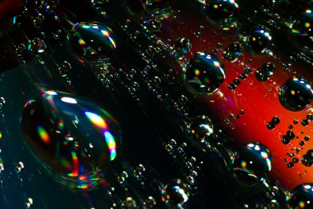 Multi-coloured drops on an iridescent surface