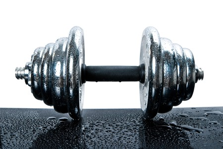 Steel dumbbell covered with drops on a black surface