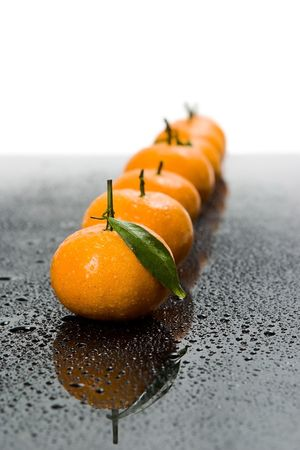 Tangerines lie in a row on the black Stock Photo