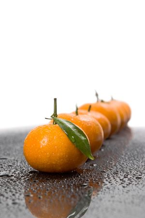 Tangerines lie in a row on the black photo
