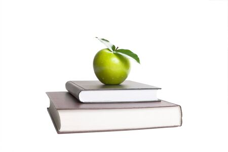 Books and green apple. White background