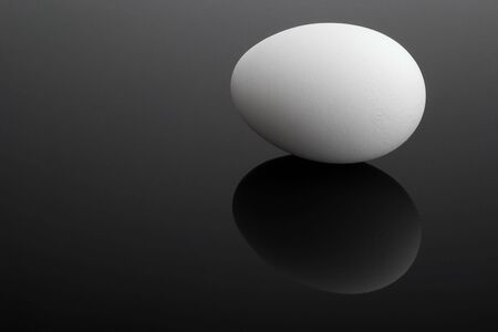 Reflected fresh white egg on a black glass Stock Photo