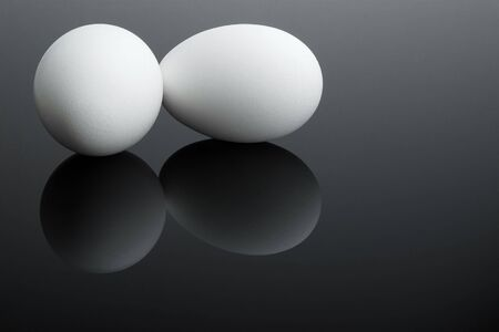 Reflected fresh white eggs on a black glass photo