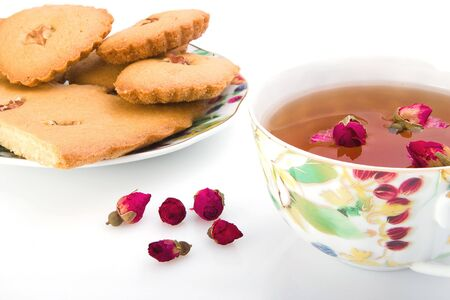 Tea with roses and a biscuit with nuts photo