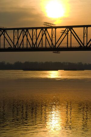 Sunset over the river and the crossing bridge