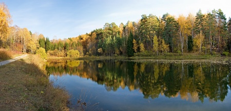 Autumn panorama, reflection in the lake, golden leaves