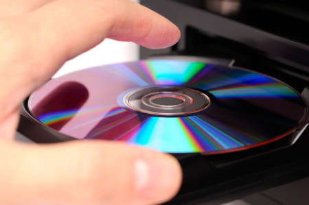 inserting: Inserting a disc into a DVD or CD player Stock Photo