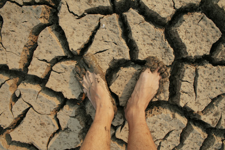 metaphoric: close up legs stand on cracked earth, metaphoric for climate change and pollution. Stock Photo