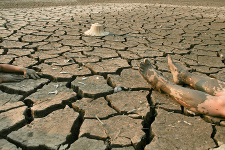 metaphoric: Dead man on cracked earth, metaphoric for climate change and pollution.
