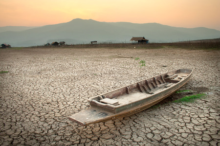 land pollution: The wood boat on cracked earth, metaphoric for climate change and global warming.