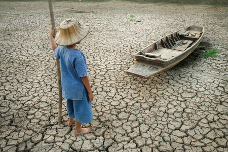 Boy looking to wooden boat on cracked earth. Reklamní fotografie - 43679550