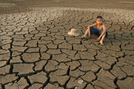 A Boy sit on cracked earth with sadness face. Archivio Fotografico