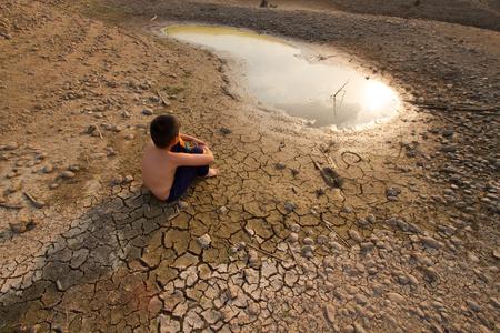 물 위기, 어린이는 건조 물 근처에 금이 지구에 앉아있다.