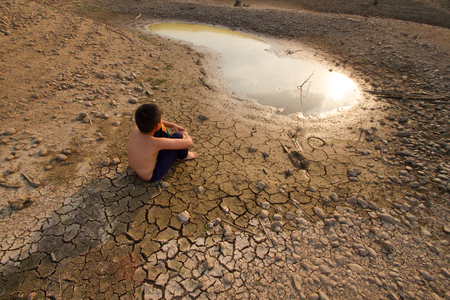 house warming: Water crisis, Child sit on cracked earth near drying water.