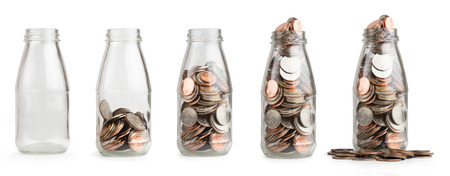 botellas vacias: Ahorrar dinero moneda en frasco de vidrio aislado.