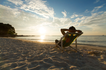 silla: El hombre se relaja en la playa silla en vacaciones con la puesta de sol y cielo azul de fondo.