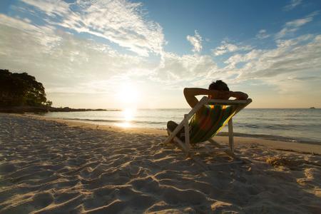 strandstoel: Man ontspannen op stoel strand in vakanties met zonsondergang en blauwe hemel achtergrond.