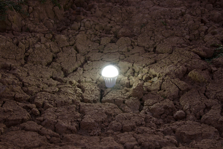 climate change: LED Light on dried land, metaphor Energy consumption problem and saving concept.