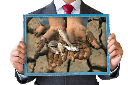 land pollution: Businessman hand holding frame with hand holding dead fish on cracked earth picture.