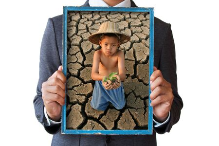 water well: Businessman hand holding frame with children looking at wooden boat on cracked earth picture.