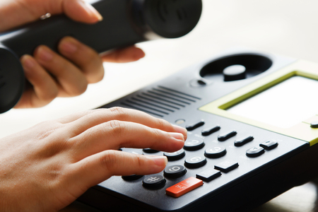 number button: Businessman hand using telephone press number button