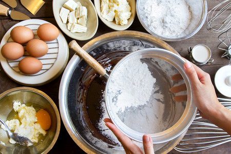 sift: Hand Sift flour, Bakery prepare for make Chocolate brownie cake, Top view Stock Photo