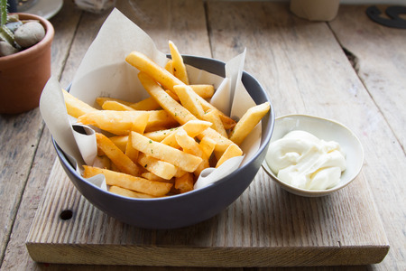 Delicious French fries or potato fries with mayonnaise on wooden background