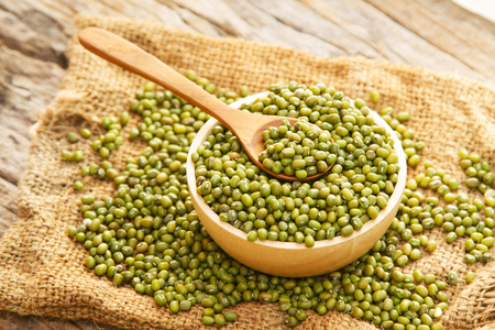 Grain Mung bean in wooden bowl and spoon on linen sack, rural agriculture and rustic organic farm concept