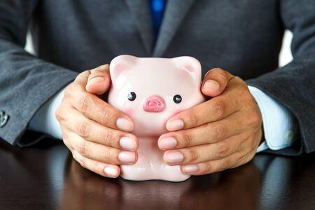 Close up Businessman hands covering piggybank Stock Photo