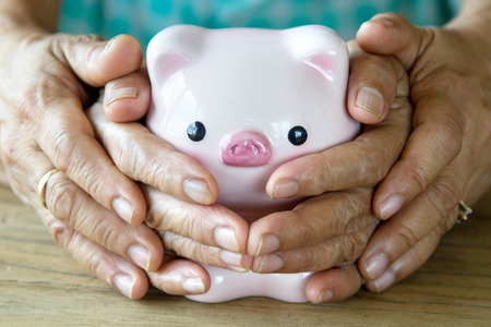 Grandmother and her daughter covering piggy bank together, metaphoric for hope, retirement, pension and life insurance. image focus at piggy bank face