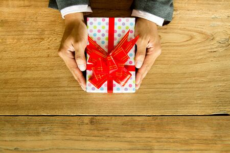 Close up Businessman giving a gift with wooden background