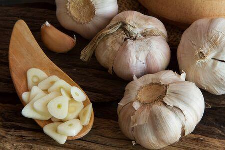 cookware: El ajo en rodajas con cabeza en la cuchara de madera y utensilios de cocina Foto de archivo
