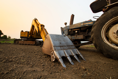 Backhoe and Tractor prepare land for cultivation with sunset sky Stock Photo