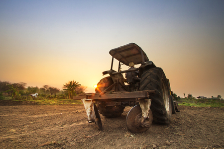 traction engine: Tractor prepare soil for cultivation with beautiful sunset at agriculture field