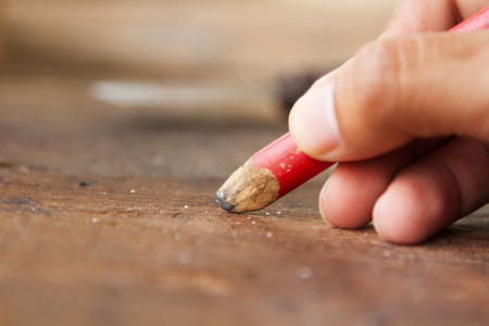 Carpenter drafting furniture by using pencil drawing to plank wood