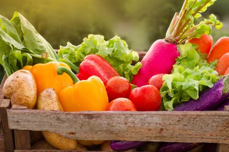 Different fresh vegetable in wooden basket at sunset. healthy eating concept