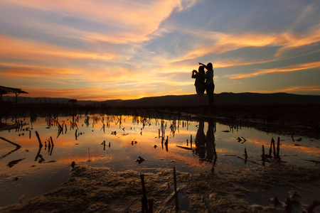 Landscape scene of two women pointing hand to sky to let her friends shooting the photo at dramatic sky of beautiful sunset.