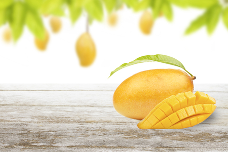 Mango fruit cut and slice put on white table with frame of green leaf and isolated background