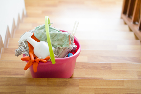 Cleaning tools in bucket on stair are prepare to cleaning whole house. House cleaning service and housekeeping concept.