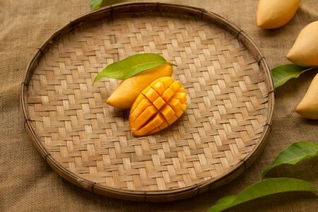 Mango tropical fruit in weave wooden basket decorated with tropical leaf