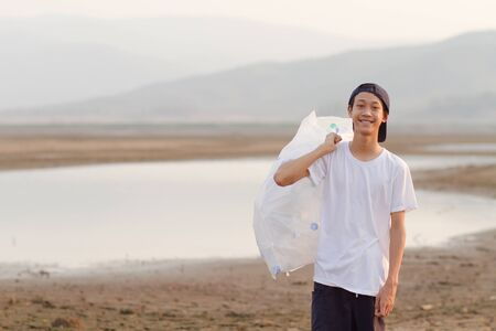 Young volunteer man hold full bag of plastic trash, collect from around river and ground with smiling and happy to participate of save environment