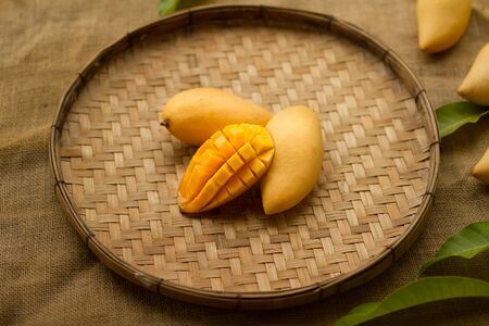 Mango fruit and mango cube sliced on wood basket with decorated of tropical leaf.