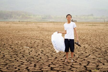 Children or young man showing many plastic bottle and bags after picking up around drying lake.