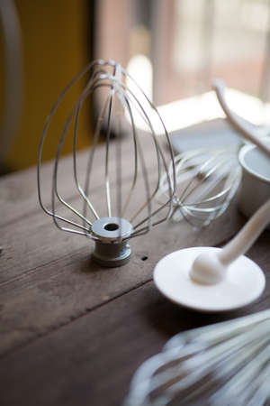 Shallow DOF of wire whisk put on wood table with many Pastry tools concept for bakery background.