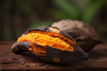 Grilled orange sweet potato put on wooden table with green nature background, Famous food in Autumn season at Japan Archivio Fotografico