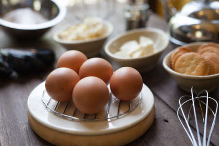 Eggs and cake or bread ingredient prepare in the cups with pastry tools on old vintage wood table with natural light at home bakery kitchen. Archivio Fotografico
