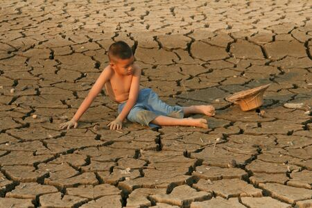 Children and Climate change, Child with sadness face sitting on dry cracked earth metaphor Drought, Environment disaster and world global warming concept.