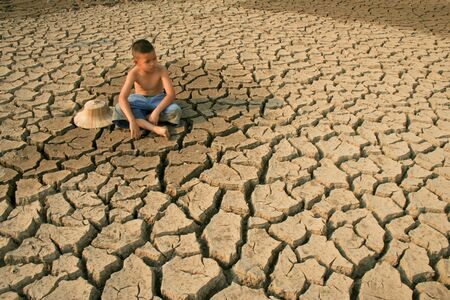 Children sitting on dry cracked earth with sadness face metaphor environment disaster, climate change and drought. Archivio Fotografico